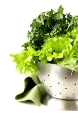 green lettuce and parsley in a metal colander