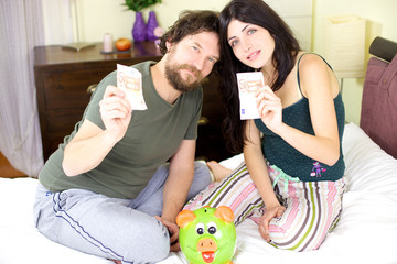 Beautiful couple showing money from piggy bank