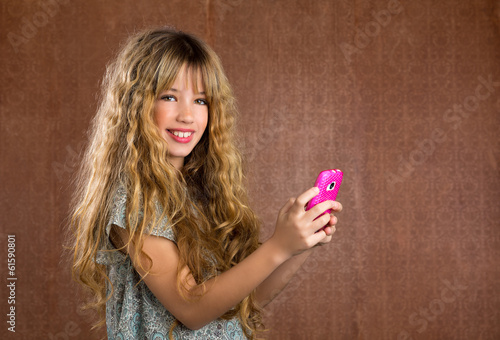 Blond kid girl playing with mobile phone vintage portrait