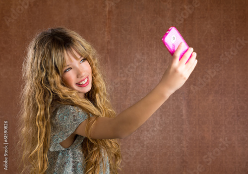 Blond kid girl taking pictures with mobile phone retro portrait