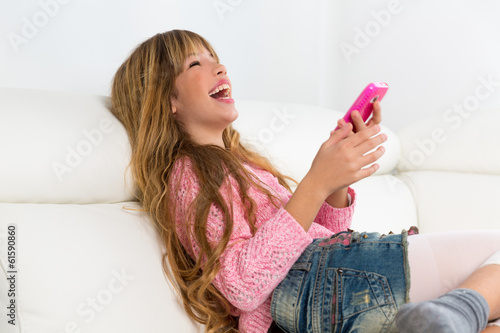 Blond kid girl playing fun with mobile phone on white sofa