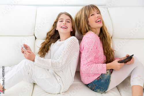 kid girls having fun playing back to back with tablet pc on sofa