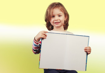 Child holding a open book on yellow-green background