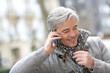 Portrait of mature man talking on phone in street
