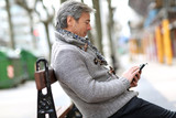 Mature man with smartphone sitting on public bench