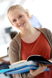 Portrait of smiling student girl holding books