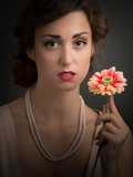 Young woman holding single gerber flower