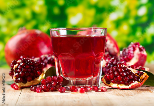 glass of pomegranate  juice with fresh fruits - 61594243