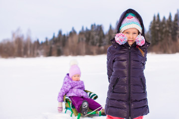 Adorable happy girl sledding her little sister