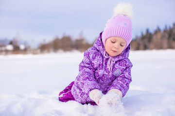 Happy little girl playing with snow at winter sunny day