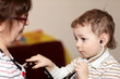 Boy examines grandmother using stethoscope