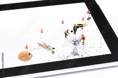 Digital tablet with broken glass and miniature of manual workers