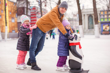 Little girls with young dad enjoying skating