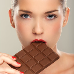 Beautiful women eating chocolate ba