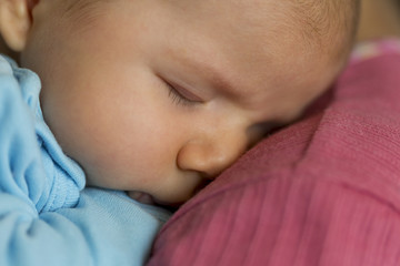 Tender scene: Cute peaceful baby boy sleeping in mother's arms.