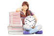 Girl holding big wall clock next to stack of books