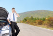 Young businessman talking on phone next to a car