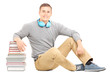 Young man with headphones leaning on stack of books