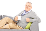 Relaxed mature man laying on sofa and drinking tea