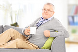 Relaxed gentleman laying on sofa and drinking coffee, indoors