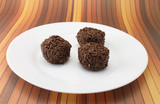 Three chocolate truffles on a white plate