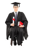 Young male graduate student sitting on chair and holding diploma