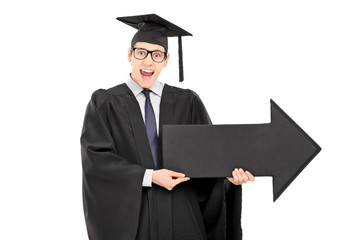 Male student in graduation gown holding big black arrow