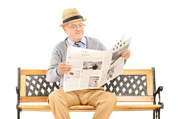 Senior gentleman reading newspaper on a bench