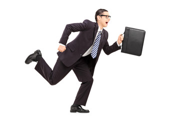 Young businessman holding a briefcase and running