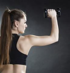 Fitness girl training shoulder muscles lifting dumbbells back