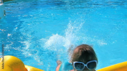 Little girl swimming on inflatable beach mattress.