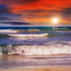 sea ​​waves breaking on the sandy beach at sunset