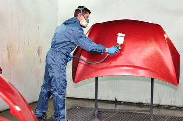 Worker painting a red bonnet.