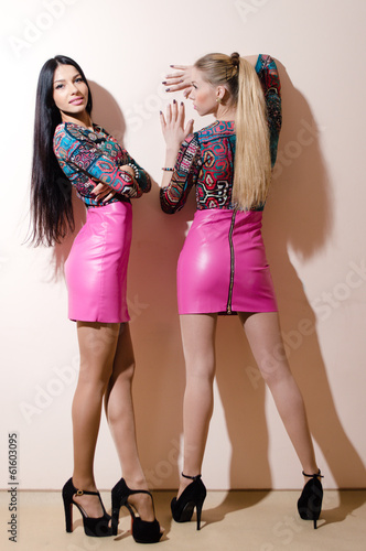 Two beautiful young women wearing same bright leather dresses