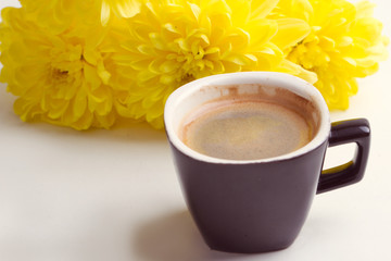 black coffee near the yellow flowers