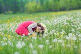 Happy little girl playing on the field of dandelion flowers