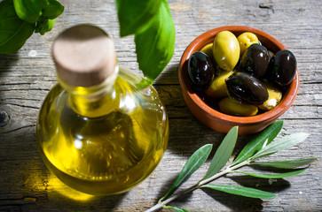 Olivenöl und Oliven serviert auf rustikalem Holztisch
