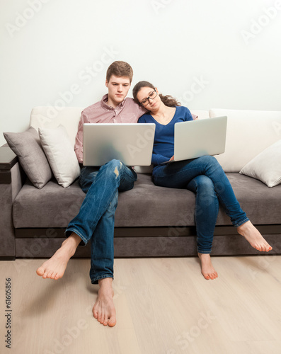 Young couple in love sitting on couch and using two laptops