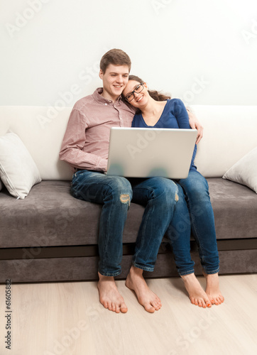 couple in love sitting on couch and watching movie on laptop