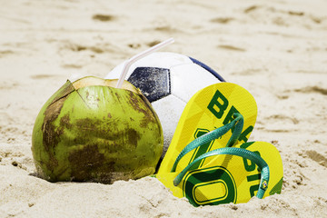 Coconut, Soccer ball and Flip flop with Brazil sign on the sand