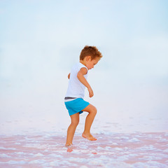 boy walking in salted pink firth lake