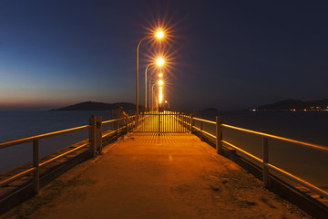 Jetty at sunset with star shaped streetlights