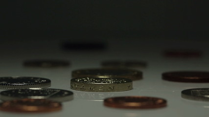 British One Pound coin spins amidst other UK currency coins