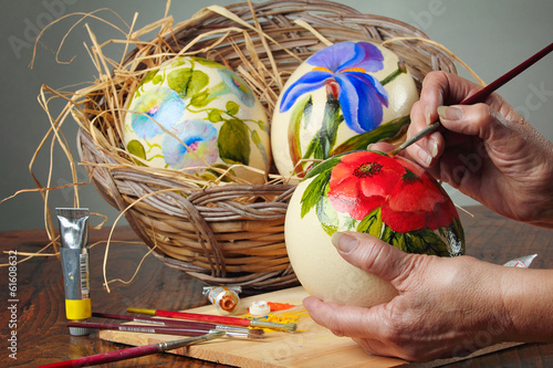 Hands painting flowers on ostrich eggs