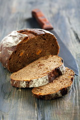 Rye bread with dried apricots and a knife.