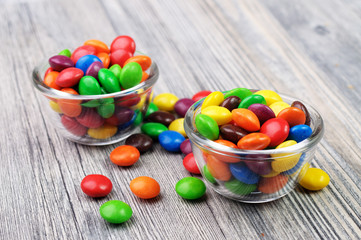 Colorful coated chocolates in two glass bowls