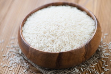 Wooden bowl with raw basmati kernels, close-up