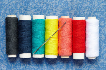 Colorful spools of thread with needle located as a rainbow