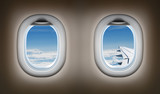 Two airplane windows. Jet interior.
