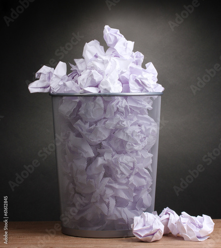 Metal trash bin from paper on wooden floor on gray background